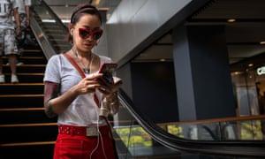 Woman on smartphone on escalator