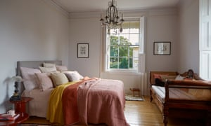 The bedroom in muted colours with many cushions on the bed and a large window