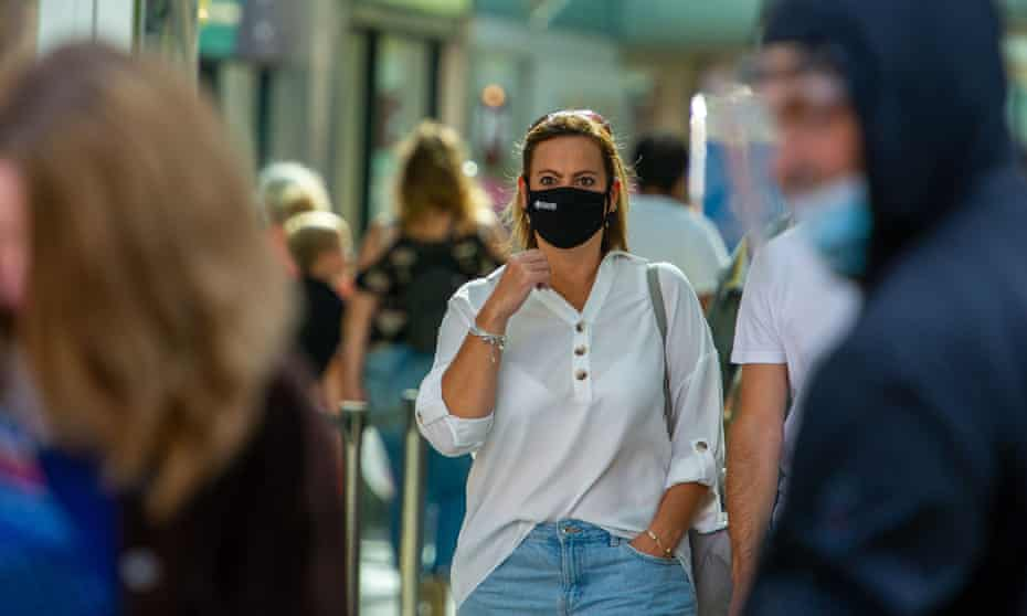 High street with a woman wearing a face mask