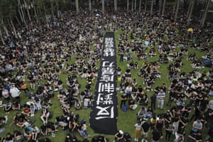 "People gather at Belcher Bay Park as they take part in an anti-extradition bill protest in Western district in Hong Kong, on Sunday with a banner reads ""Against institutional violence, we want real elections."""