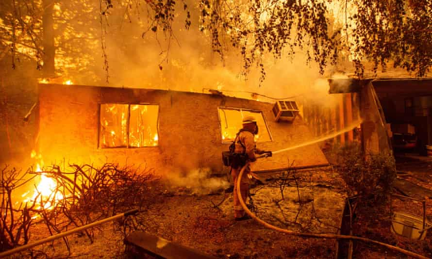 Ffirefighters battle flames at a burning apartment complex in Paradise, California, on 9 November.