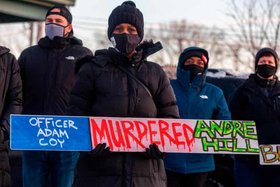 A demonstrator holds a sign condemning officer Adam Coy at a candlelight vigil for Andre Hill on 26 December in Columbus, Ohio.