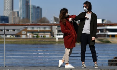 People wearing face masks as a precautionary measure against covid-19 'elbow bump' as they stand in Greenwich in south London, backdropped by the Canary Wharf financial district, on March 24, 2020