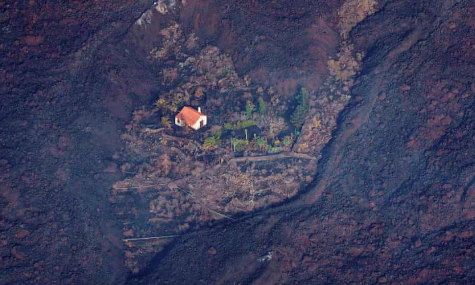 Lava flows surround a house following the eruption of a volcano in the Cumbre Vieja national park at El Paso, on the Canary Island of La Palma