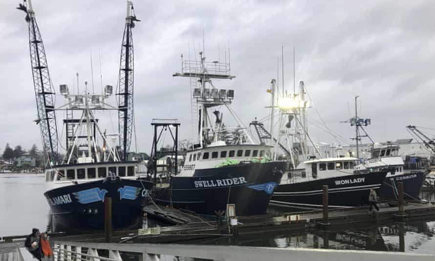 Trawlers that fish for groundfish off the Oregon and Washington coast are shown in the background as a fisherman walks up a ramp from the docks in Warrenton, Oregon.