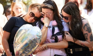 Three young women comfort each other at the memorial to the Manchester attack victims