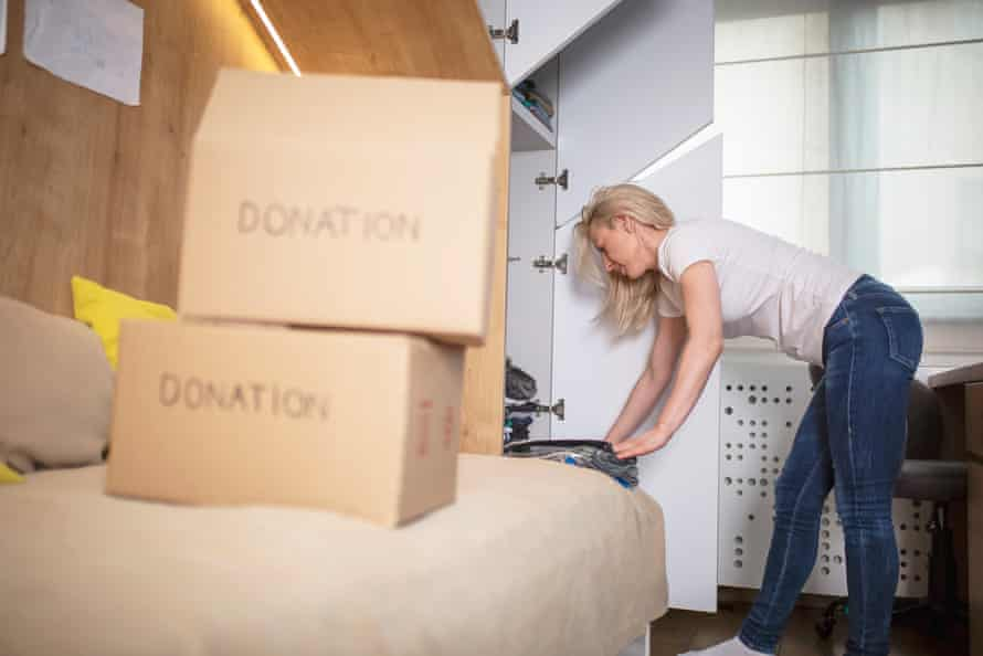 Woman sorting clothes from her sons closet for donation