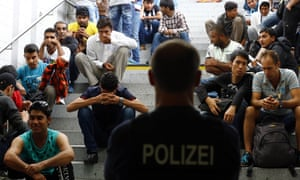 Refugees wait for registration after arriving Germany at the main station in Rosenheim on Tuesday.
