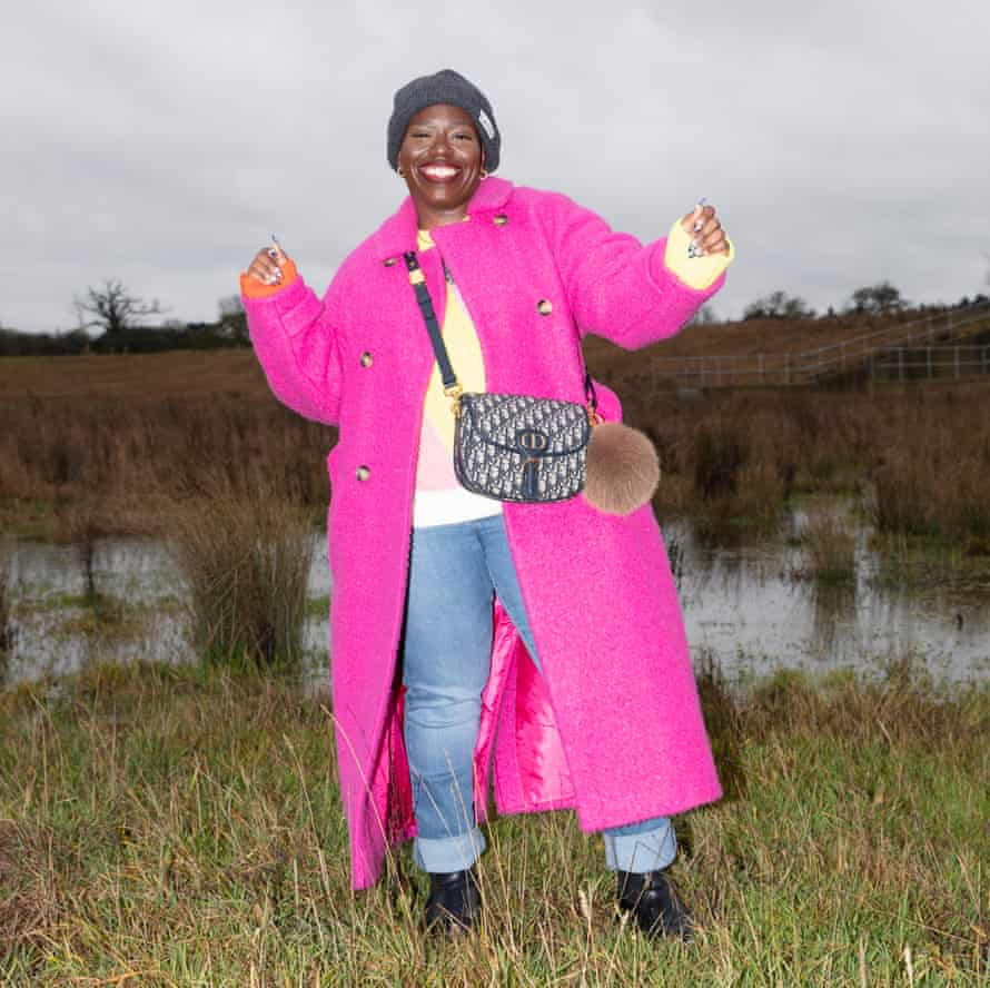Candice Brathwaite wearing jeans, a jumper and a shocking-pink coat