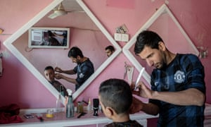 'Business has never been better,' says Mosul  physics student turned barber Ahmed Taher Majid, above, putting the finishing touches to Saif Rayan, 14.