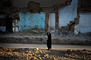 A woman walks past a destroyed building in Kandahar, a ruin symbolic of Afghanistan's general insecurity.