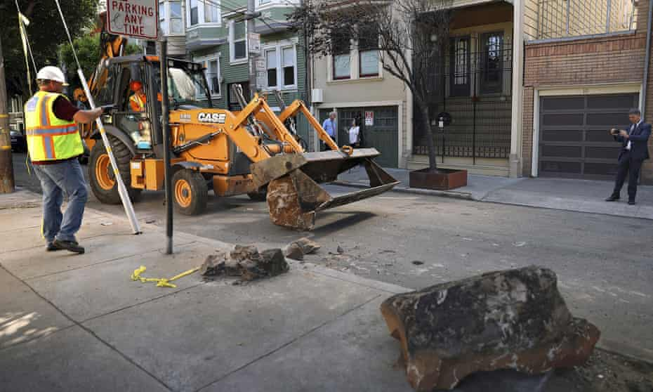A San Francisco public works crew removes boulders from a sidewalk along a street in the Clinton Park alley, 30 September 2019.
