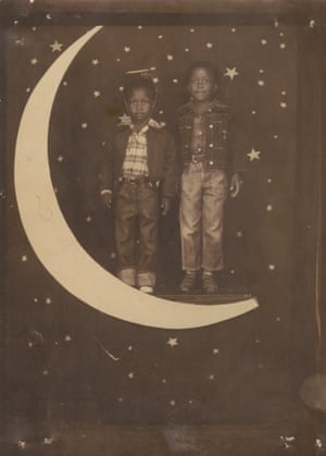Two African American boys, one wearing a hat, standing on crescent moon with starry backdrop