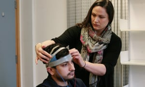 Researcher Jennifer Chesters fitting electrodes to Naheem Bashir's head