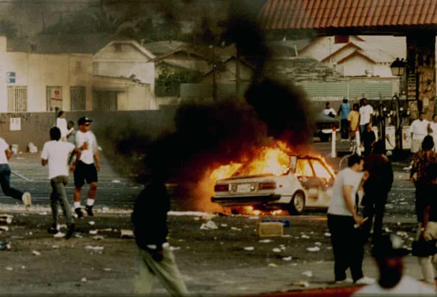 A car burns as looters take to the streets at the intersection of Florence and Normandie Avenues in 1992.