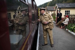 World War II reenactors speak with train passengers as they attend the 25th 'Railway in Wartime Event' along the line of the heritage 'North Yorkshire Moors Railway' at Levisham Station, near Pickering, northern England