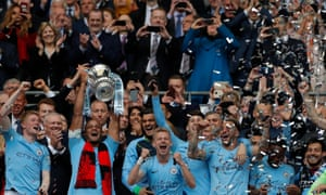 Manchester City's Vincent Kompany lifts the trophy as his teammates celebrate.