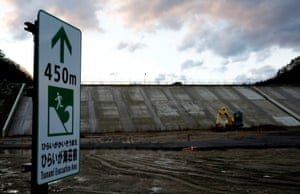 A sign pointing to a tsunami evacuation area stands in front of a sea wall in Tanohata
