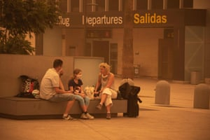 Passengers waiting outside Tenerife South airport after flights were cancelled due to the sandstorm