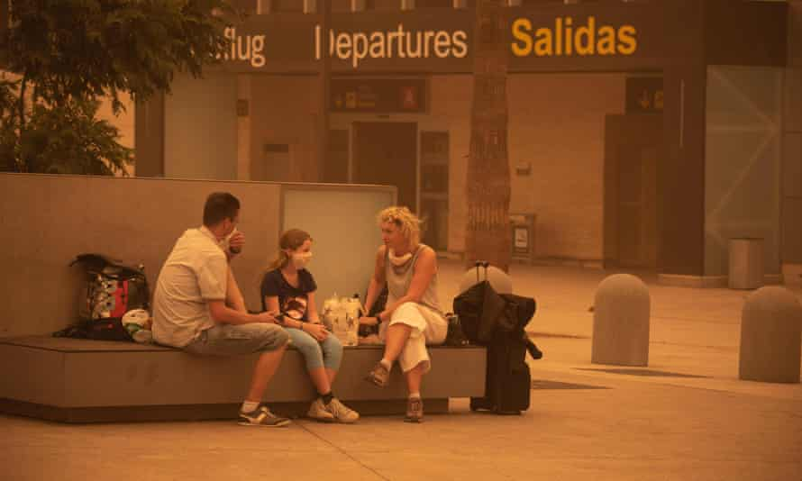 Passengers waiting outside Tenerife South airport after flights were cancelled due to a sandstorm on Sunday.