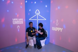 A couple share a light moment while sitting on toilet bowls