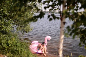A boy takes to the water with an inflatable flamingo