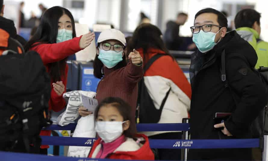 Passengers wearing masks wait in a line to check-in to a flight