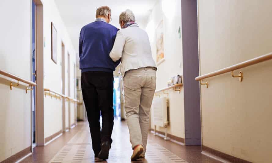 Senior couple walking a corridor in a care home