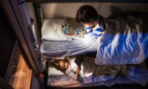 Children in bed in a couchette compartment on the Thello train from Paris
