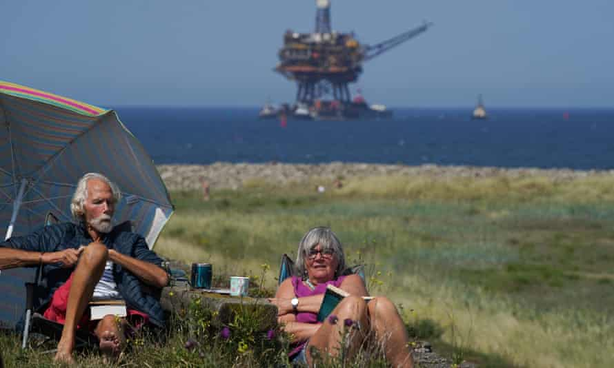 Couple picnicking with North Sea oil platform in distance