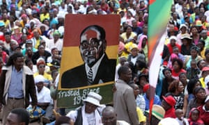 Robert Mugabe's supporters carry his portrait while gathering in Harare on 20 July.