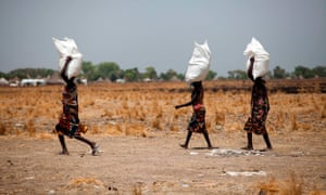 Three women carry sacks of food distributed in South Sudan