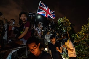 A pro-democracy supporter waves a British flag as protesters gather on Lion Rock.