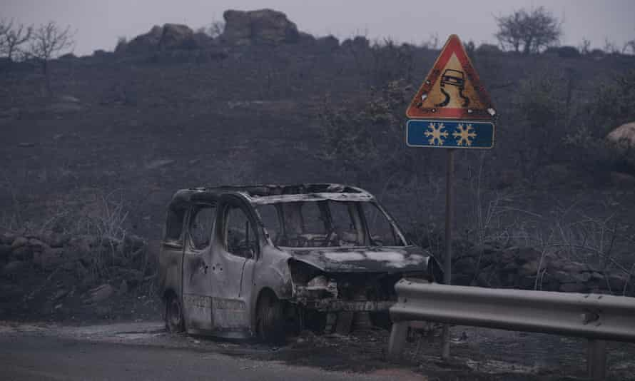 A car left destroyed by the blaze in the province of Oristano