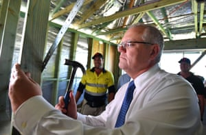 Prime Minister Scott Morrison hammers a nail at an investment property development in Port Macquarie on Thursday.