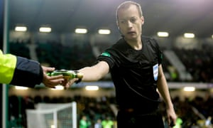 Referee Willie Collum hands a steward a bottle thrown from high in the stands as Celtic's Scott Sinclair prepared to take a corner.