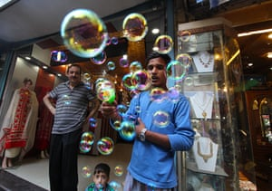 A street vendor blows soap bubbles to attract Eid customers at a local market