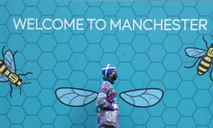 A person wearing a face mask walks past a Welcome to Manchester mural.