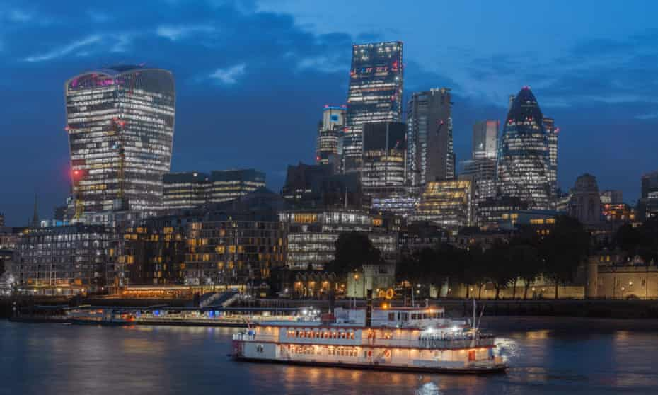 A boat passes by the City of London at night.