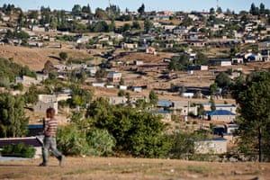 A young boy walks down a dirt track in a suburb of Maseru, Lesotho