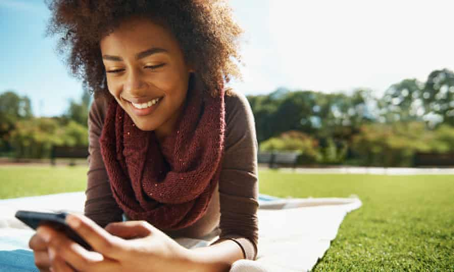 Shot of a smiling young woman relaxing with her phone in the park