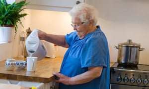 Lady in kitchen making tea using a kettle.