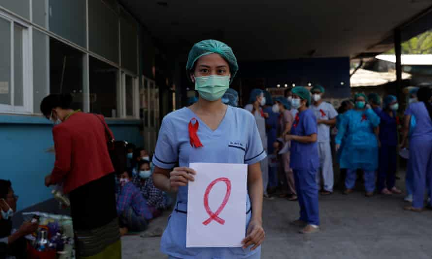 A member of medical staff wearing a red ribbon on her uniform holds a sign as a symbol of resistance against the military coup in Myanmar