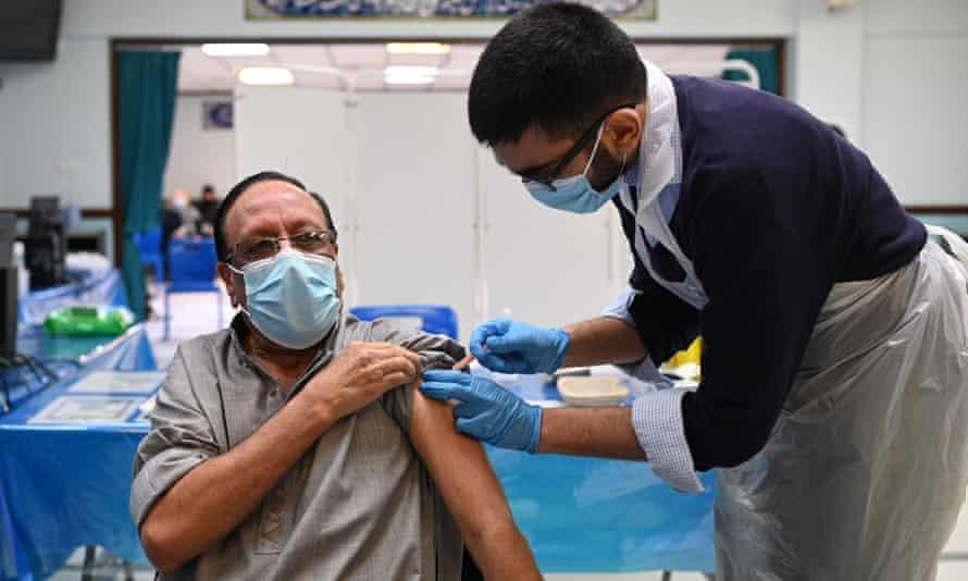 A pharmacist administers a dose of the Oxford/ AstraZeneca Covid vaccine at the Al-Abbas Islamic Centre in Birmingham.