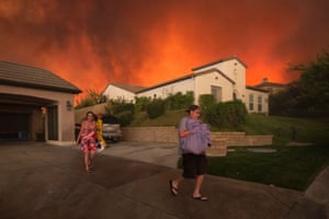 Residents flee their home as flames from the Sand Fire on 23 July 2016 near Santa Clarita, California.