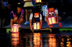 Children release lanterns in the river to offer prayers for the victims of Japan Airlines jumbo jet crash at Ueno village in Japan