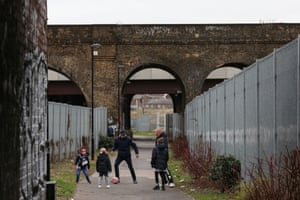 Three young boys and their dads play football beneath the arches of a railway bridge as they make their way to the match between Millwall and Rochdale AFC at The Den. Millwall score a 90th minute equaliser to level the score 2-2 anf face a replay at Spotlands.
