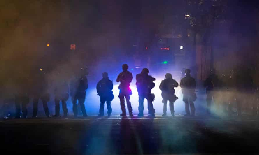 Federal officers walk through teargas while dispersing a crowd of about a thousand people during a protest on Tuesday in Portland, Oregon.