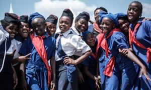 Members of Kenya Girl Guides take photos after attending ceremony of the International Women's day at Kawangware in Nairobi, Kenya.