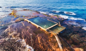 Remote isolated rock pool off Mona Vale beach at high tide with swimmer breaking waves of Pacific ocean coast in Sydney.